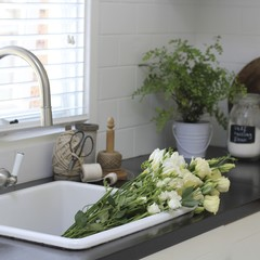Bunch of flowers in kitchen sink
