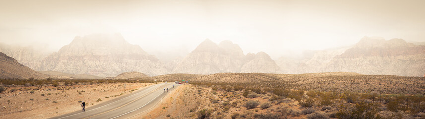 USA, Nevada, Clark County, Bonnie Springs, Red Rock Canyon National Conservation Area, Mountain range and bikers on road