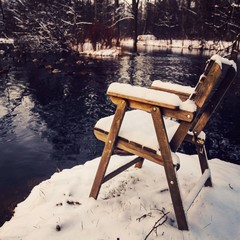 Snow covered chair by river