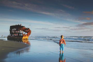 Boy (4-5) walking towards shipwreck
