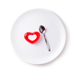 jelly in the form of heart with a spoon on a white plate