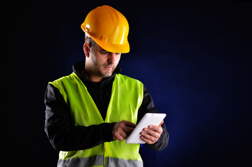 Young engineering with orange helmet working on a tablet pc