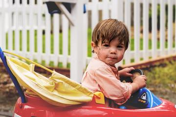 Boy ( 2-3 ) in toy car