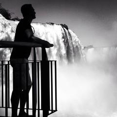 Brazil, Man looking at mighty waterfalls of Iguazu