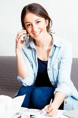Young woman using phone while working on home finances