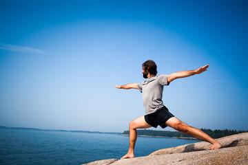 USA, man doing yoga at seaside