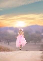 Little girl (4-5) wearing pink dress running in landscape