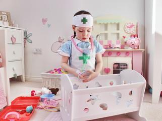 Girl (4-5) playing dress up as nurse