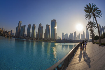 Dubai lagoon with skyscrapers against sunset in UAE