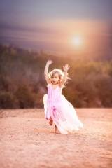 Girl (4-5) running at sunset
