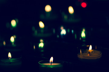 Lit tealights in darkness