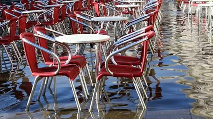 chairs and tables in a restaurant in venice during high tide