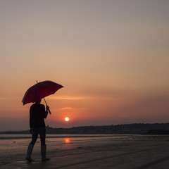 Person waking with umbrella on beach at sunset