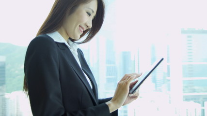 Female Asian Chinese Stock Broker Mini Tablet Close Up