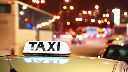 Shining Taxi inscription against passing cars on night street