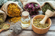 Healing herbs in hessian bags, mortar with chamomile and essenti - 77410061