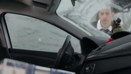 Guy trying to clean the icy windscreen finding a damaged dot