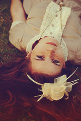 Portrait of red hair woman laying on grass