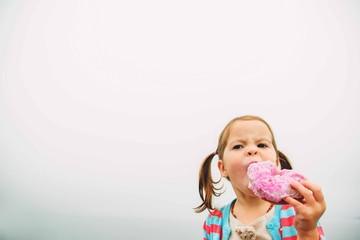 Girl (2-3) eating donut