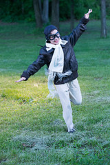 Boy running through yard pretending to be airplane