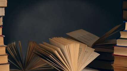 Old books on wooden deck table and dark background. UHD, 4K