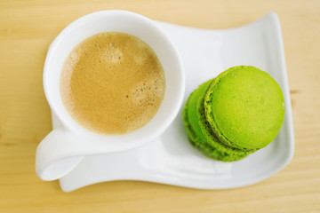 Overhead view of cup of coffee and two French macaroons on tray