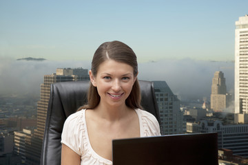 Portrait of young businesswoman in office with office buildings in background