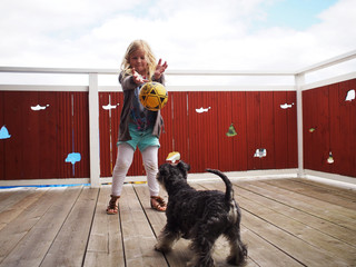 Young girl (6-7 years) playing with dog