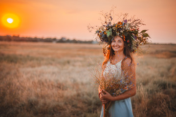 Beautiful young woman with flowers in the field