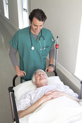 Doctor moving patient in bed along hospital corridor
