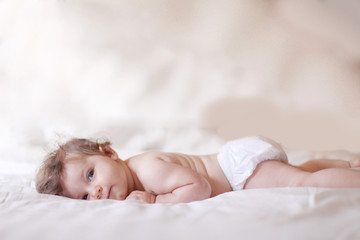 Baby girl lying down on bed and looking at camera