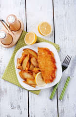 Breaded fried fish fillet and potatoes with sliced lemon