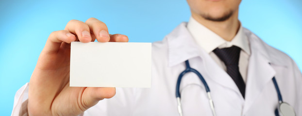 Male doctor with card on blue background