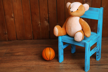 Bear toy on chair on wooden background