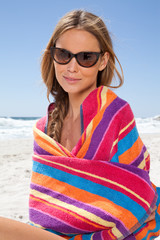 South Africa, Young Woman sitting on the beach wrapped in a beach towel