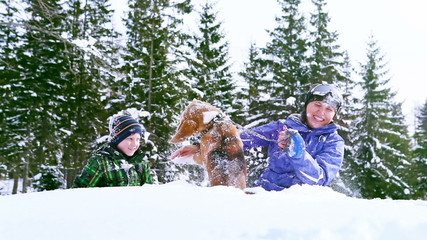 Mother and son playing with beagle dog in deep snow
