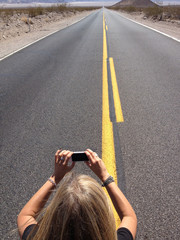 USA, Nevada, Woman taking photo of infinity road with cell phone