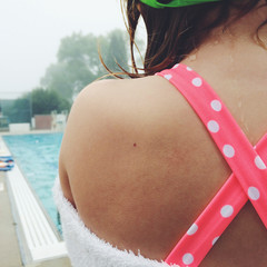 Rear view of girl (8-9) standing by swimming pool
