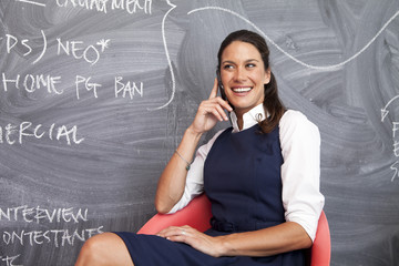 Woman Sitting By Blackboard