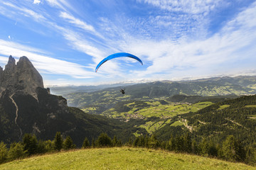 Paraglider flying over mountains