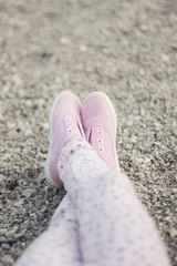 Legs in pink sneakers on sand