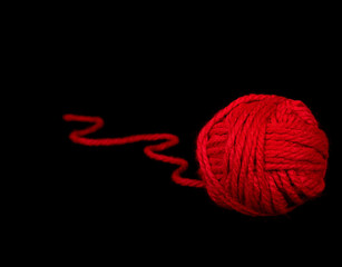 red ball of yarn on black