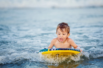 Little boy (2-3) on surfboard