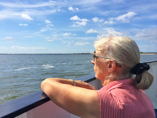 Senior woman on boat looking out to sea
