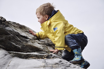 Boy in raincoat climbing on rocks