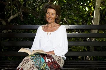 Senior woman reading book in garden