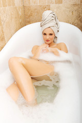 Woman relaxing in bathtub.