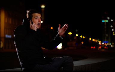 Germany, Berlin, Portrait of young man talking on phone on street at night