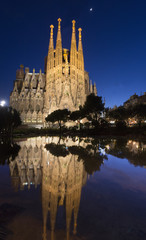 Spain, Barcelona, Sagrada Famillia, Cathedral reflecting in pond at night