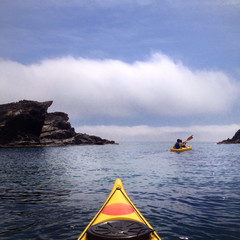 Spain, Costa Brava, Kayaking among cliffs